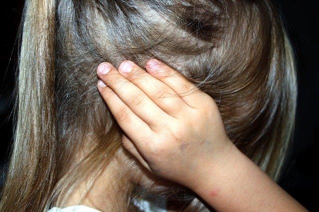 Mała dziewczynka zakrywa uszy